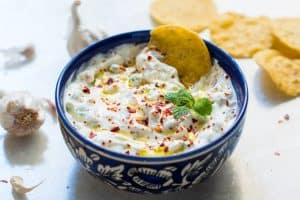 A close up of A picture of Garlicky yogurt party dip served in a blue bowl with chips