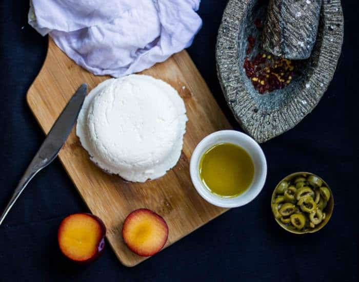 A picture of Homemade Cream Cheese on a wooden board along with Olive oil and Plum.