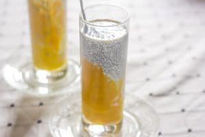 The Mango Chia seed breakfast drink served in a glass with a spoon.