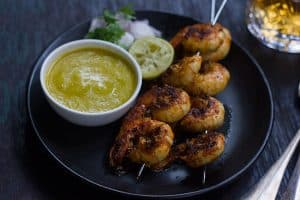 Tandoori Prawns served with mango chutney, onions and lemon in a black plate.