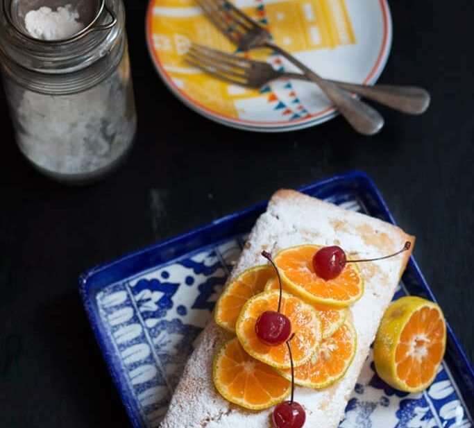 Orange Buttermilk Pound Cake loaf served on a blue and white plate.