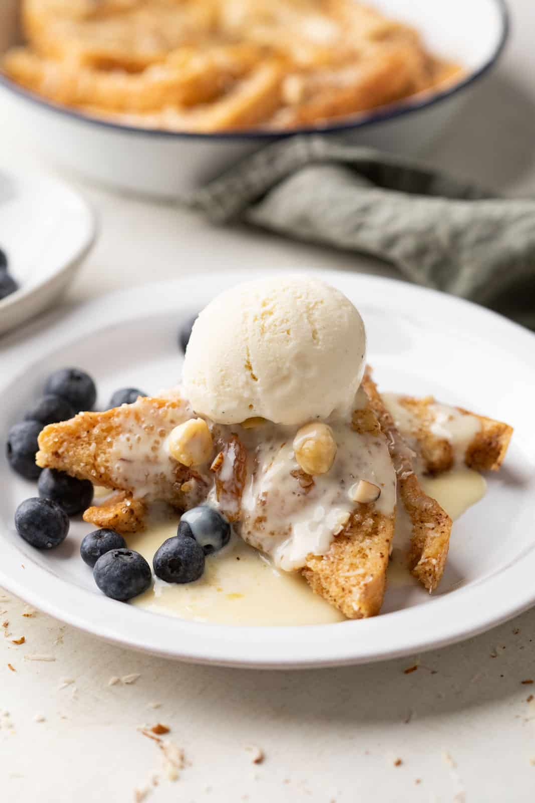 Cinnamon bread pudding served on a plate topped with rum custard sauce and a scoop of ice cream