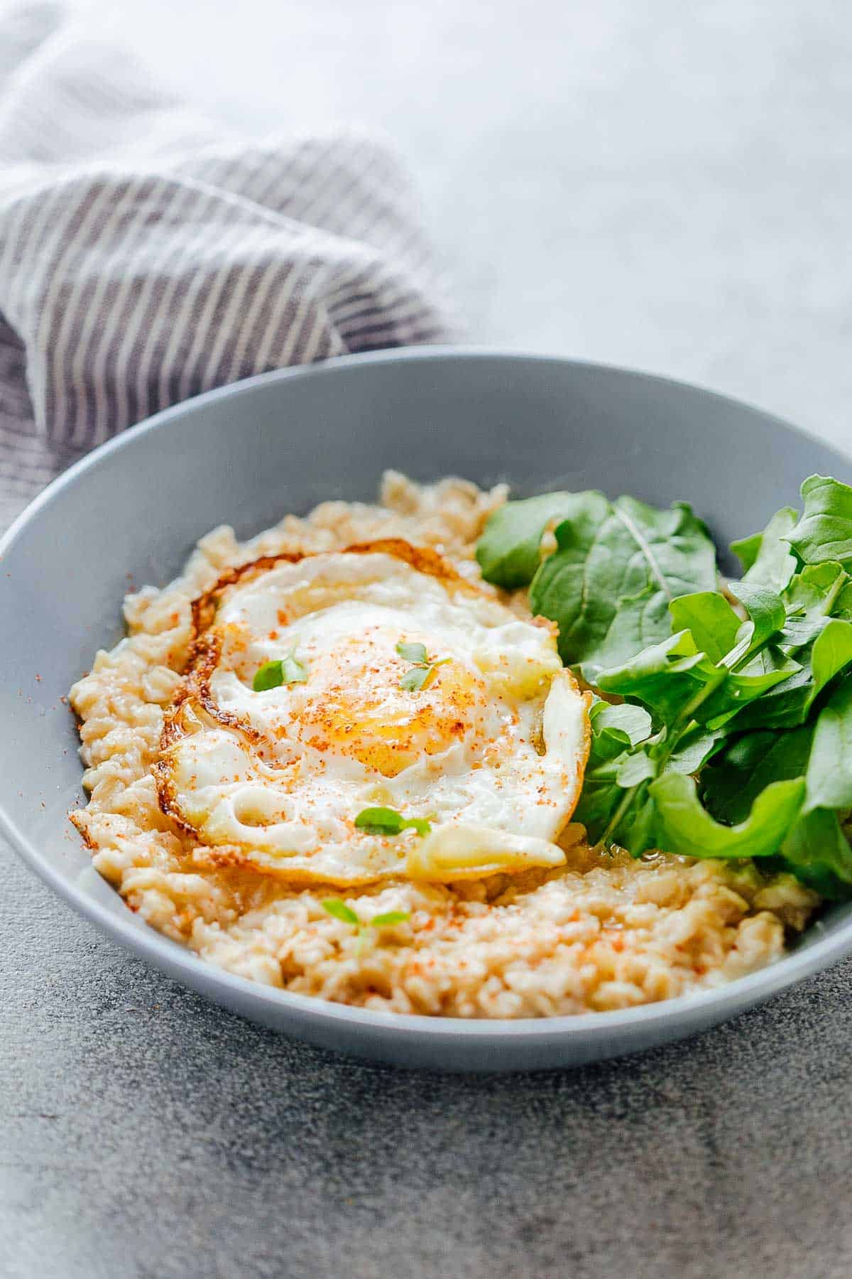 Savory Garlic Oats with Masala Fried Egg in a bowl with mixed lettuce greens