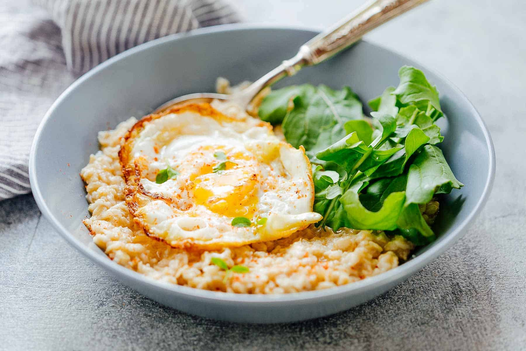 hese savory garlic oats with a masala fried egg are healthy, delicious and a great way to switch up breakfast when you are bored of regular sweet oatmeal. The runny yolk adds a gorgeous creaminess and the crispy edges add crunch. Make it a breakfast salad bowl with mixed greens or toss it up with some spices for a really satisfying breakfast.