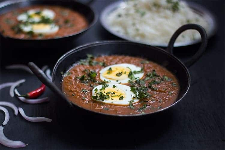 The egg curry garnished with coriander and served with rice.