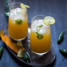 Tall Mango Jalapeno Fizzy Cocktail served with ice and a slice of lime in glasses resting on a brown tray.