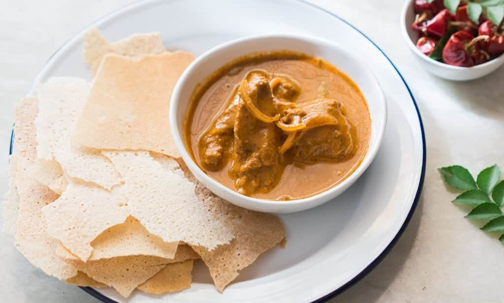 Chicken Kori Rotti served in a white plate.