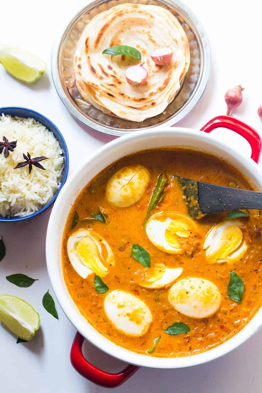 South Indian Style Egg Curry in a pot with steamed rice and malabar parathas