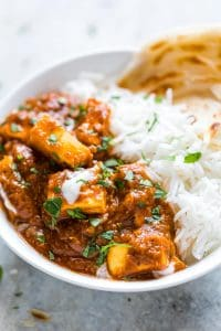 Restaurant Style Paneer Butter Masala served with a side of parathas and jeera rice.