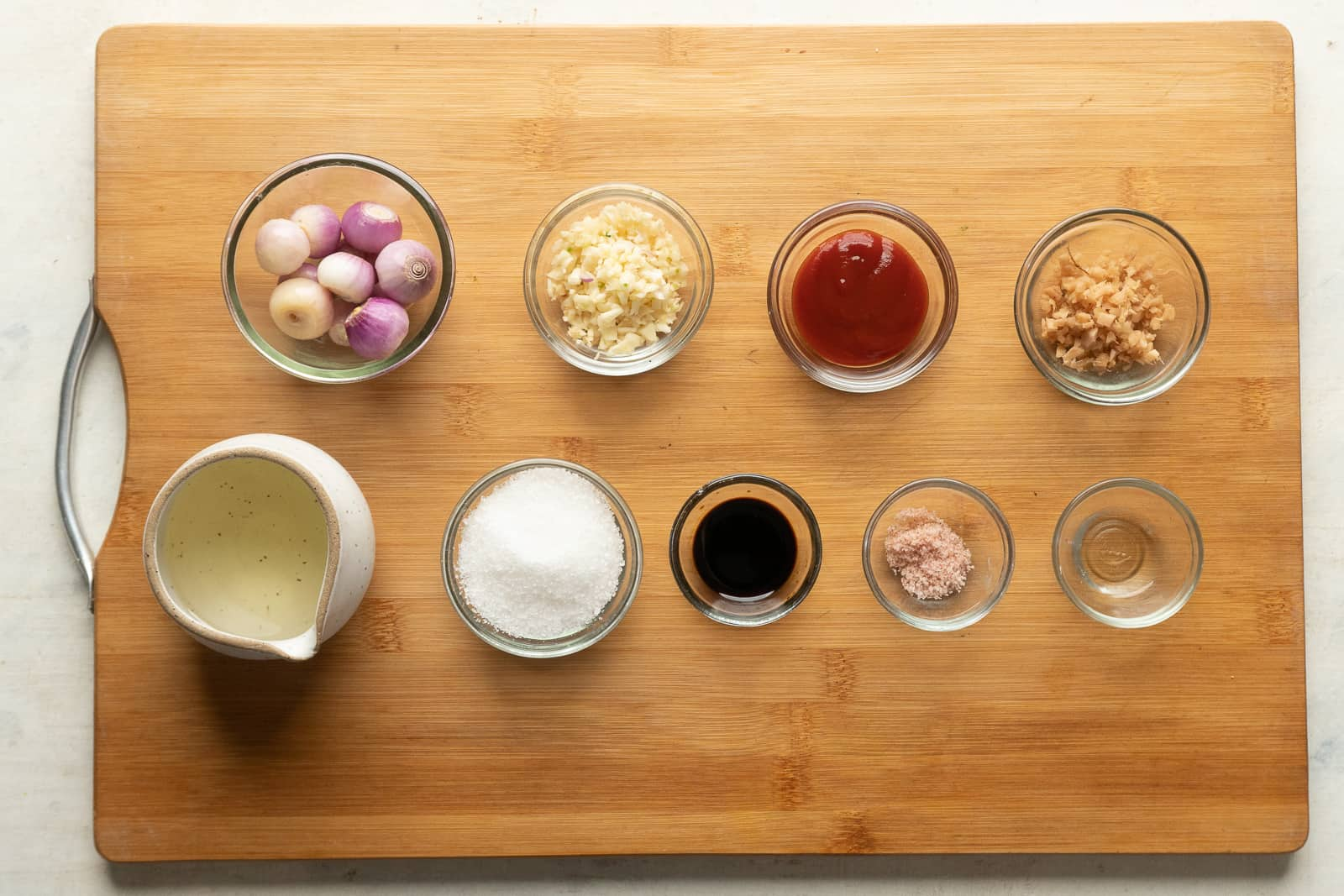 All the ingredients required for schezwan sauce are pictures on a wooden board, except chillies and hot water