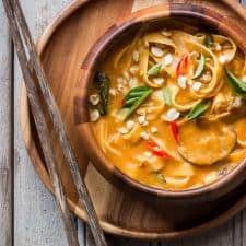 Creamy, comforting spicy thai curry pumpkin noodle soup served in a bowl.