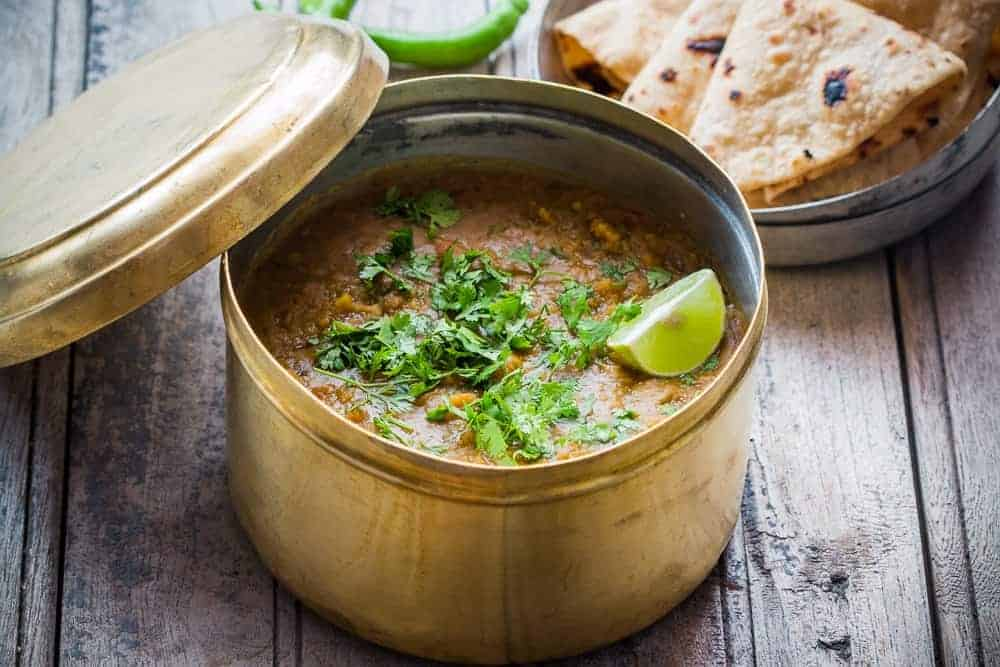Dhaba Style Dal Fry garnished with lime, coriander and served in a dabba with a side of rotis.
