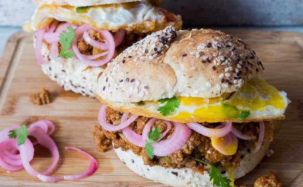 The Keema Pav Burger/ Indian Lamb Sloppy Joes served on a wooden board.