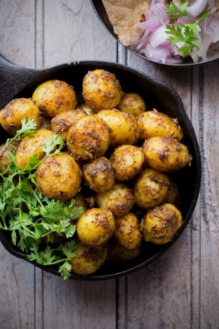Bombay potatoes garnished with coriander and served in a black pan.