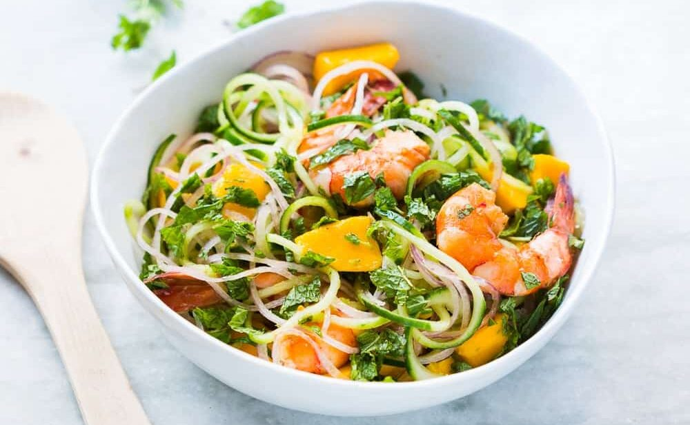 Cucumber Noodle Prawn and Mango Salad served in a white bowl.