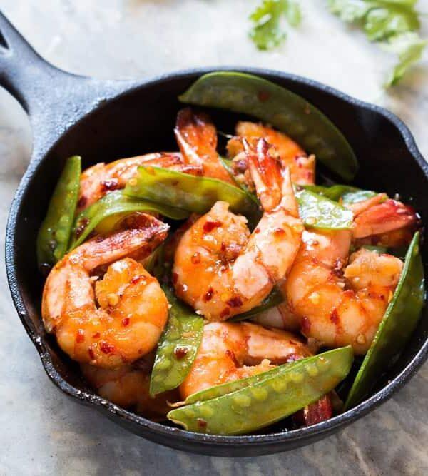 The chilli garlic prawns in a black pan.
