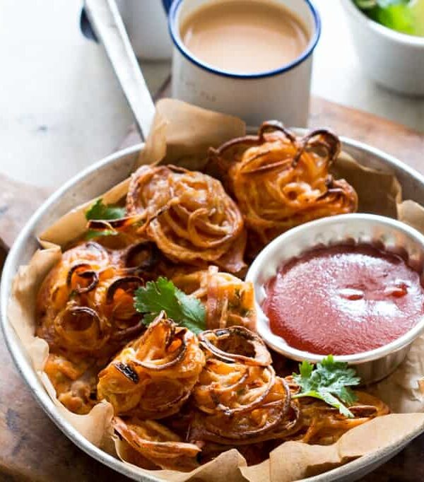 Crispy Baked Onion Pakodas (Fritters) garnished with coriander and served with sauce and chai.