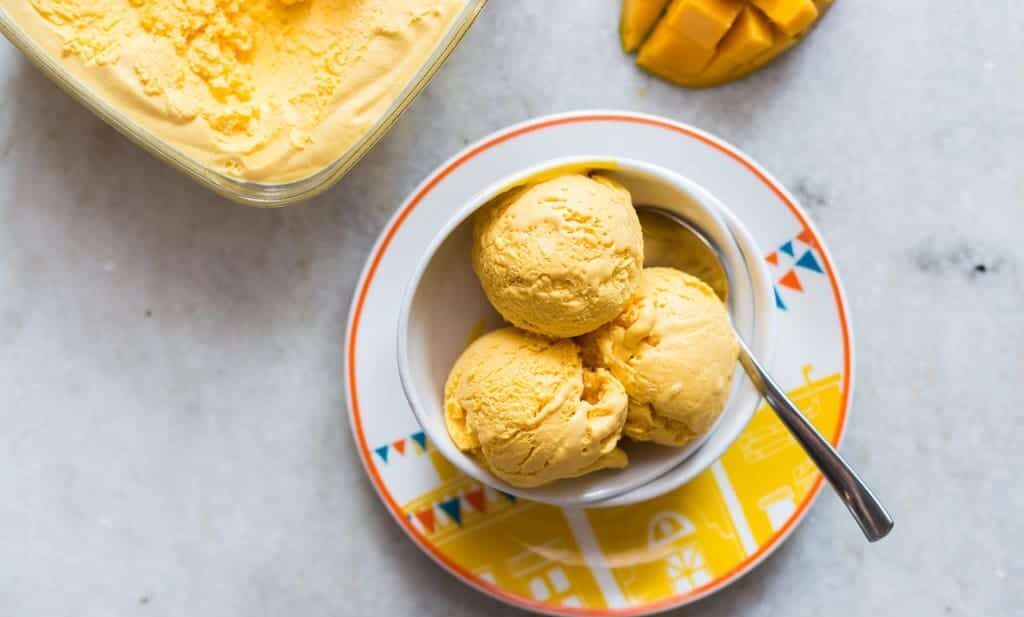 Three scoops of Homemade Mango Cheesecake Ice Cream served in a white bowl.