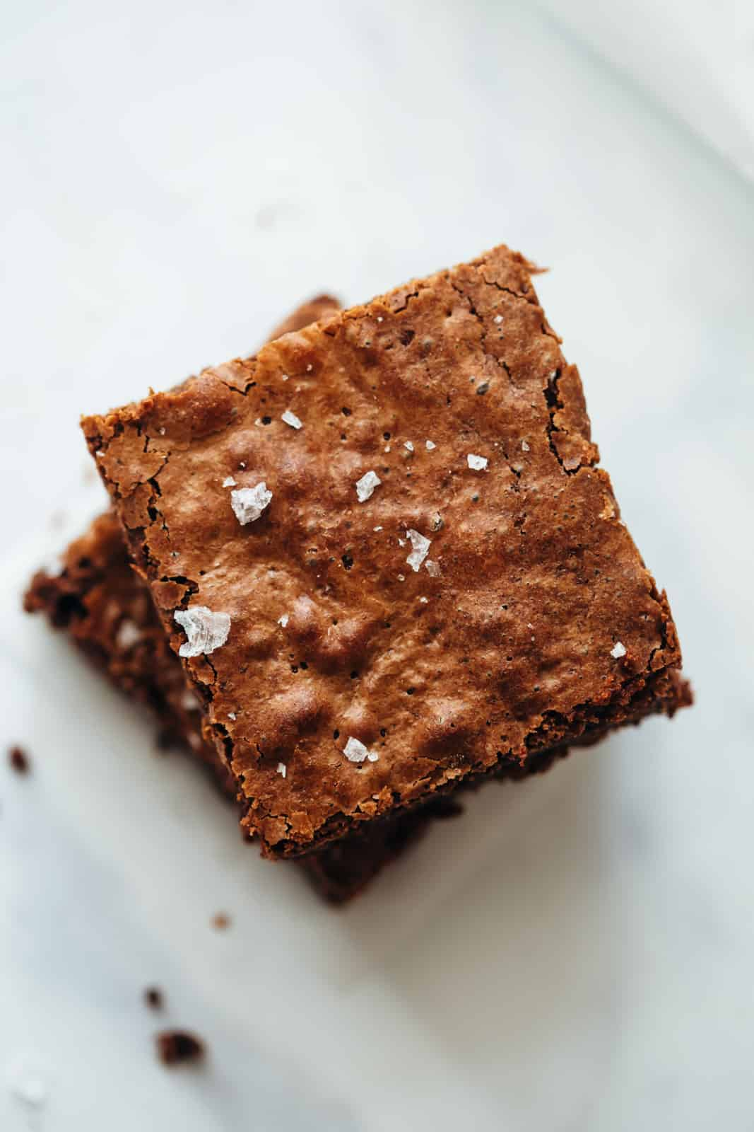 Chickpea Flour Brownies stacked one on top of the other topped with sea salt