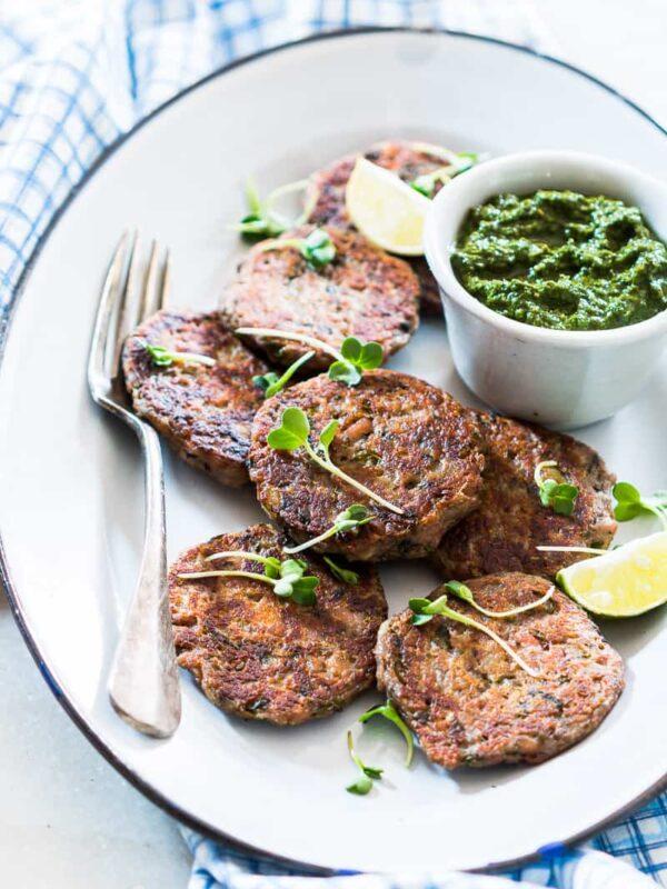 Kachhe kele ke kebab garnished and served on a white plate with a side of green chutney.