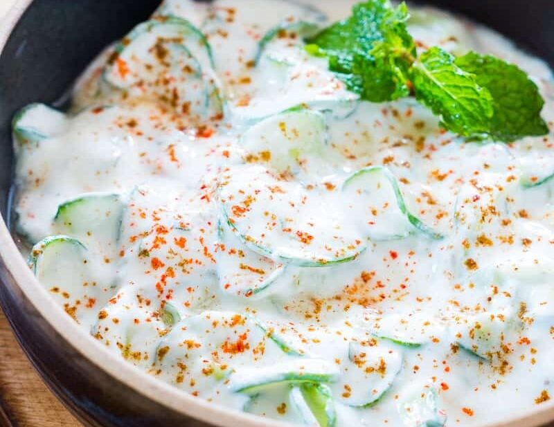 Indian Spiralized Cucumber Mint Raita garnished with some mint, masala and served in a black bowl.