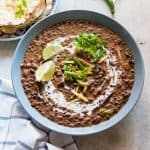 Dal Makhani topped with cream, coriander, ginger, lime and served in a blue bowl.