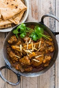 Mutton curry garnished with coriander, ginger and served in a kadhai alongside paranthas.