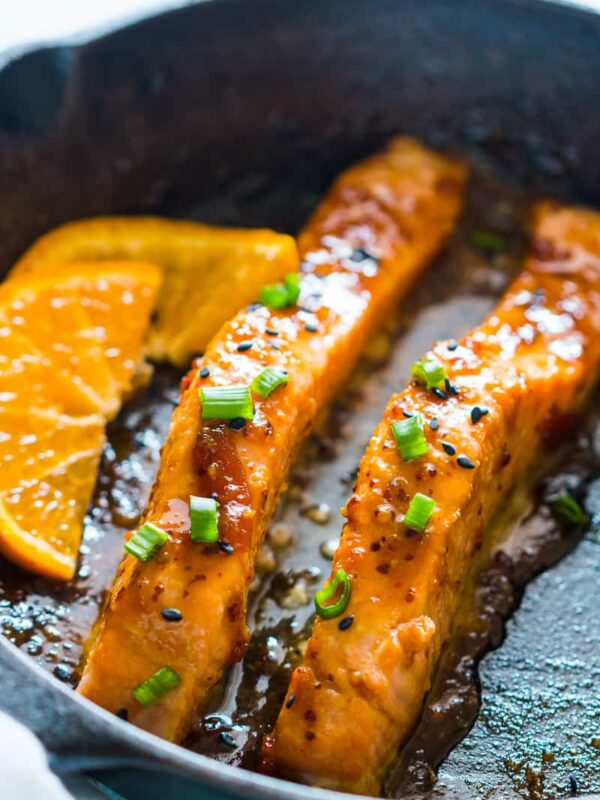 v=Orange Mustard Salmon being seared in a pan.