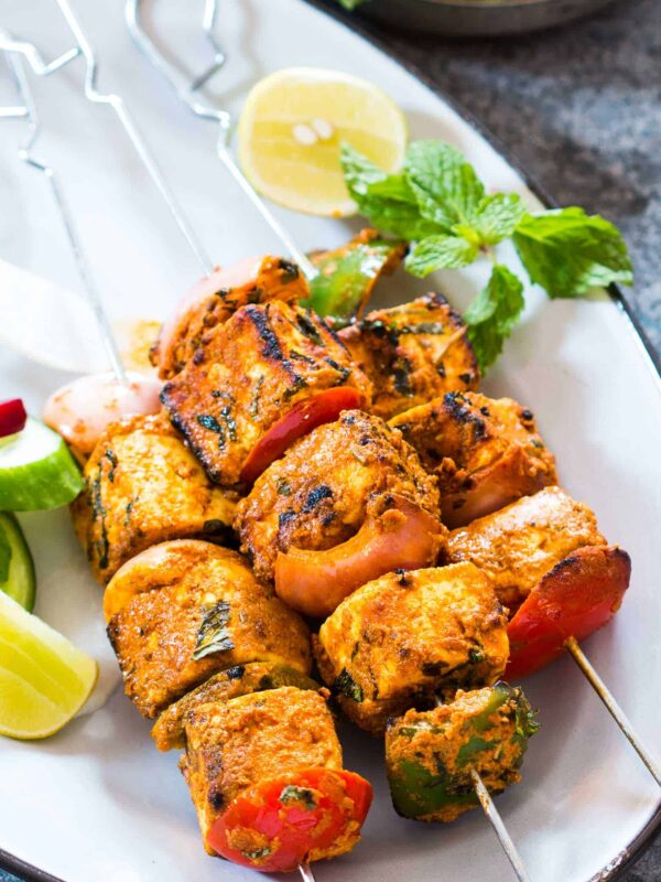 Paneer tikka skewers garnished with mint, lemon and served on a white plate.