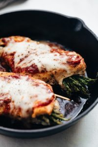 Asparagus Stuffed Chicken Parmesan topped with marinara sauce and prepared in a cast iron pan.