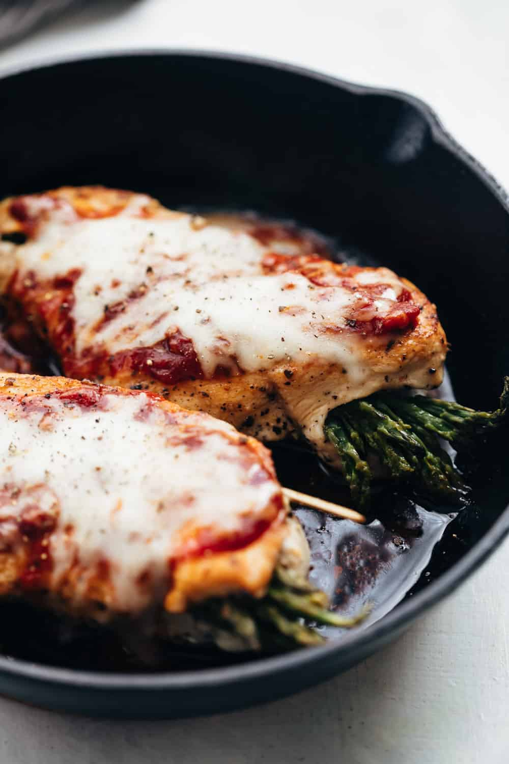Asparagus stuffed chicken parmesan served on a cast iron pan