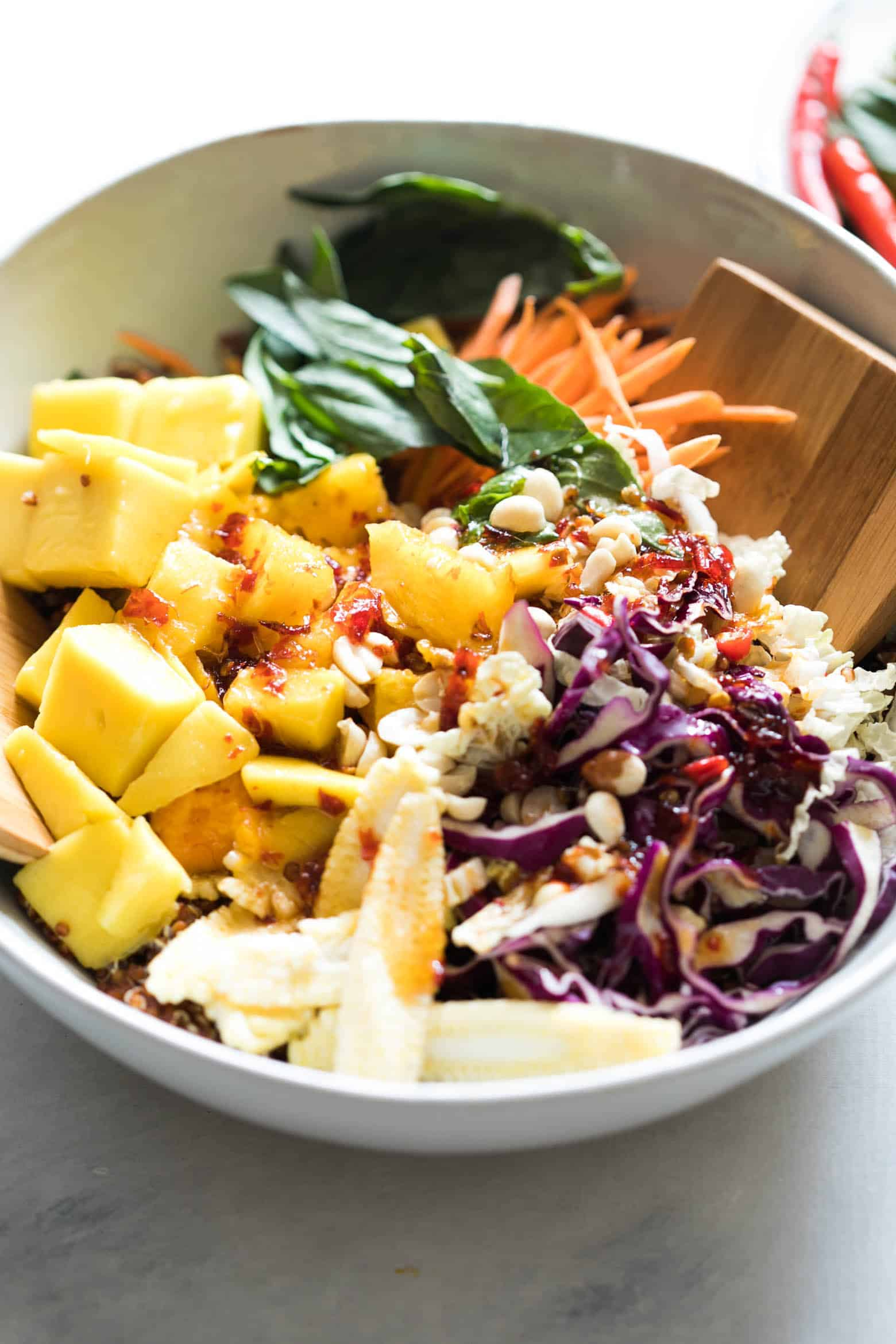 Super delicious Thai Peanut Mango Quinoa Salad which you can make ahead for potlucks and barbecues and also happens to be gluten free and vegan! Comes with a finger licking sweet and spicy sambal dressing that's different from the regular peanut dressing.