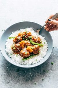 Asian inspired slow cooker teriyaki meatballs with pineapple served with steamed rice in a bowl.