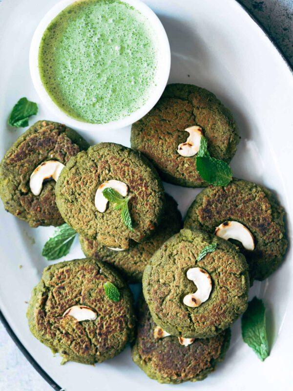 Soya Hara Bhara Kebab served with green chutney on a white plate.