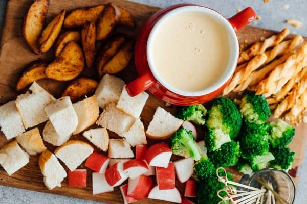 Easy cheese fondue recipe with white wine picture with fondue dippers such as bread, broccoli, wedges, radishes, bread sticks etc.