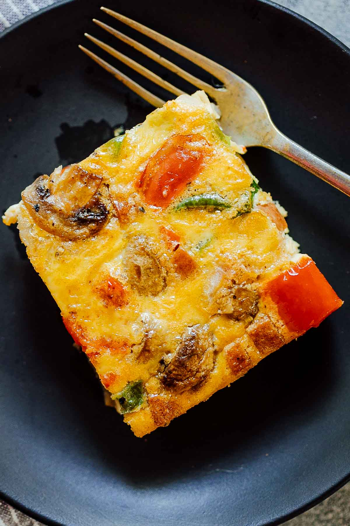 A slice of baked denver omelet breakfast casserole on a plate