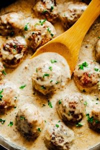 Creamy Chicken Meatballs in Mushroom Sauce with a wooden ladle.