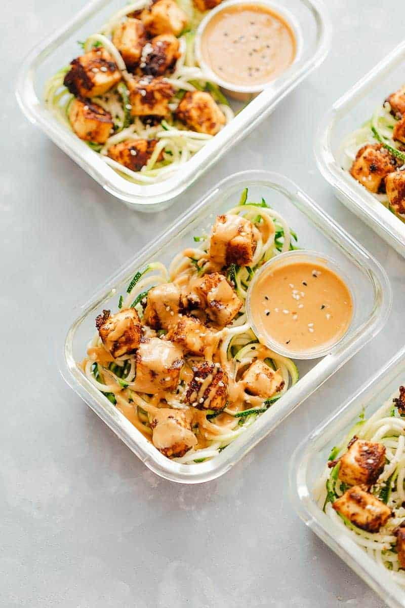 Crispy Sesame Tofu Zucchini Noodles in meal prep containers with peanut sauce