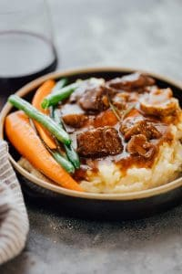 Pressure Cooker Beef Bourguignon served with mashed potatoes and grilled veggies in a black plate.