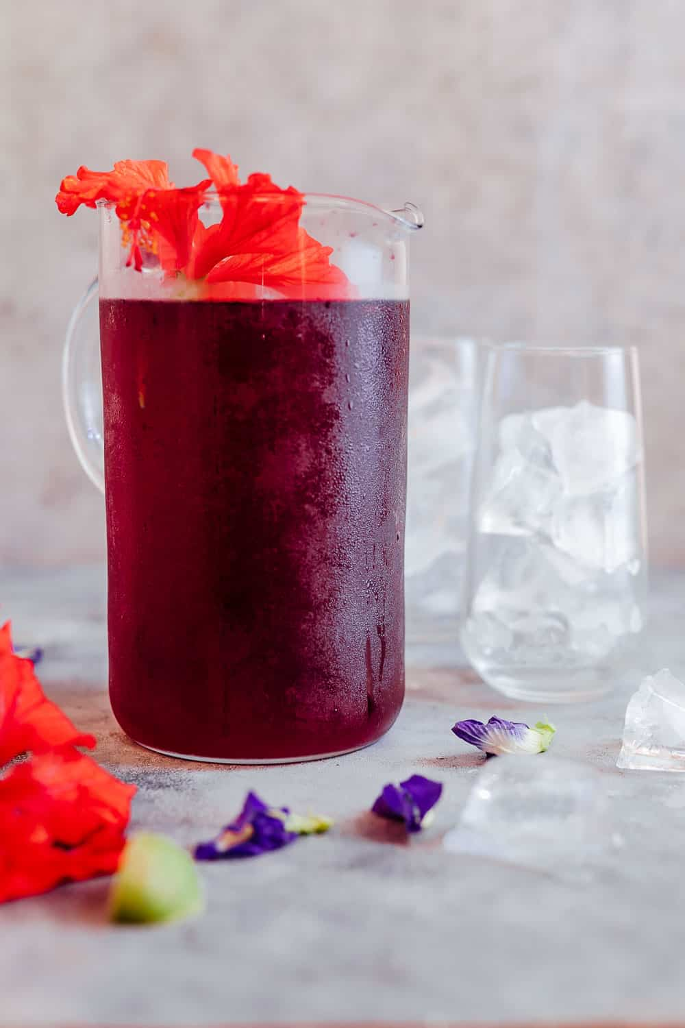 Iced Hibiscus Tea served in a large jug with fresh hibuscus flowers