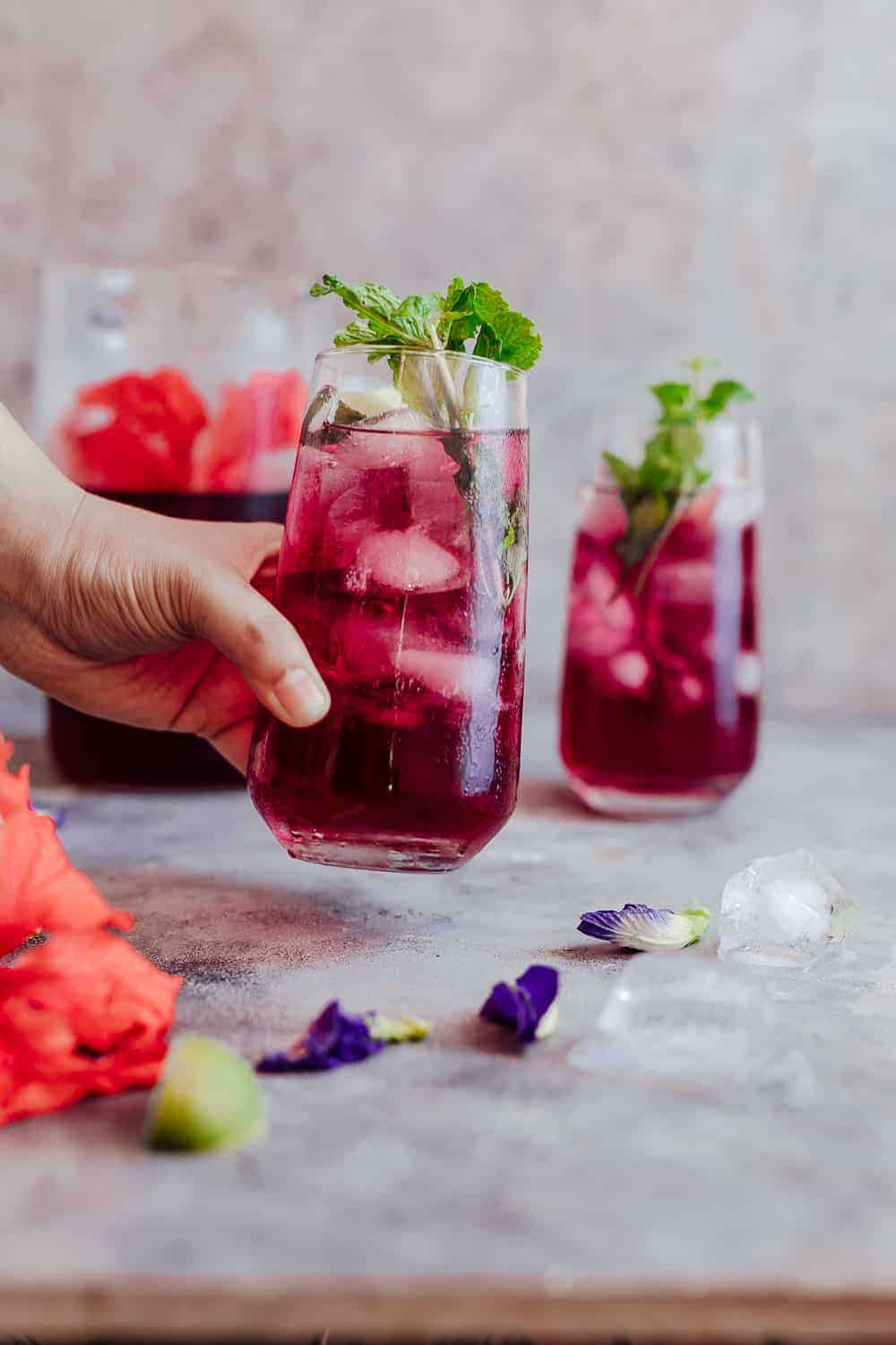How to make hibiscus tea benefits and side effects picking up a glass of chilled hibiscus tea which is served with mint leaves and lemon izmirmasajfo