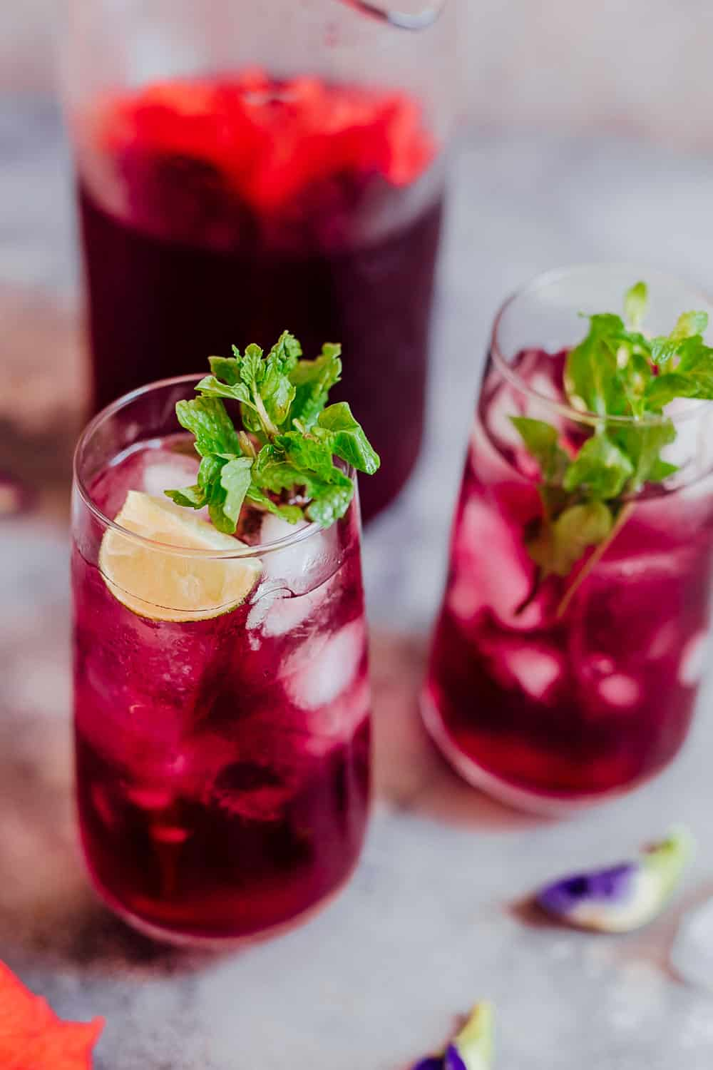 Closeup of a glass of hibiscus tea with ice cubes, mint and lemon