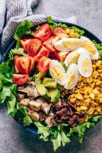 Chicken Cobb Salad served in a bowl - it has lettuce, tomatoes, chicken, bacon, corn and boiled eggs