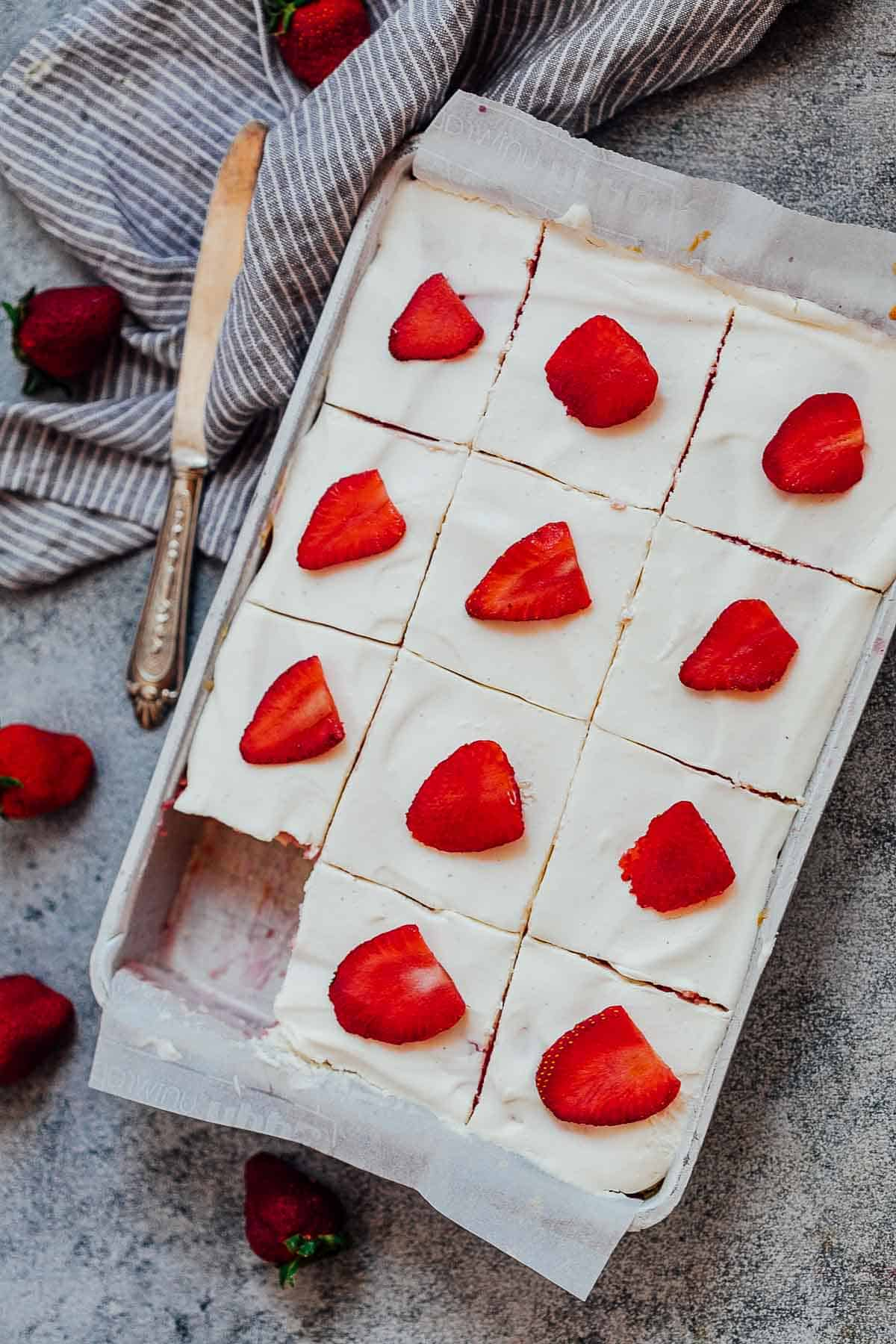 Slices of strawberry poke cake in a sheet pan with a knife and fresh strawberries on the side