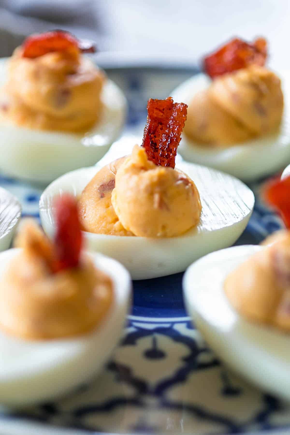 Close up of Spicy bacon deviled eggs on a blue and white plate topped with bacon