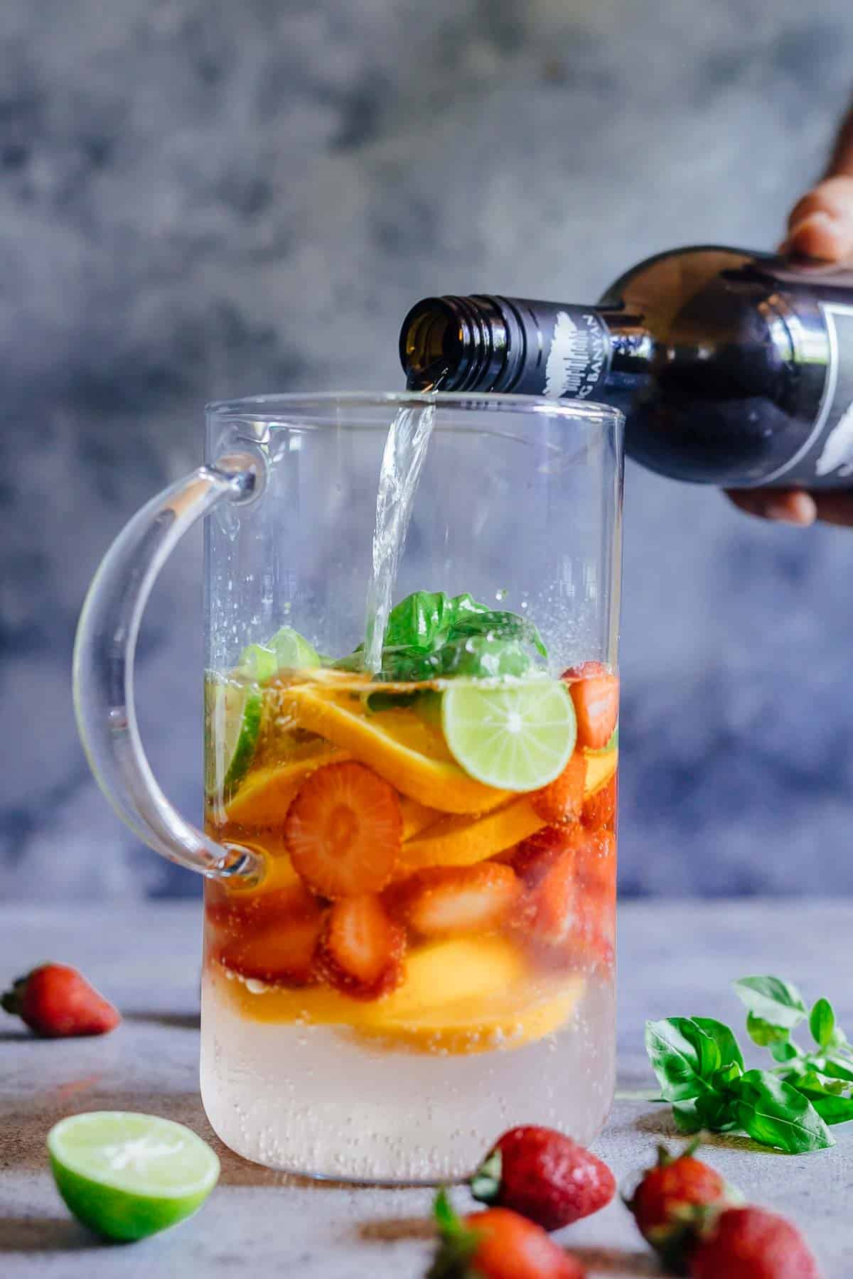 Pouring wine in a pitcher over fruits to make Strawberry Orange White Wine Sangria