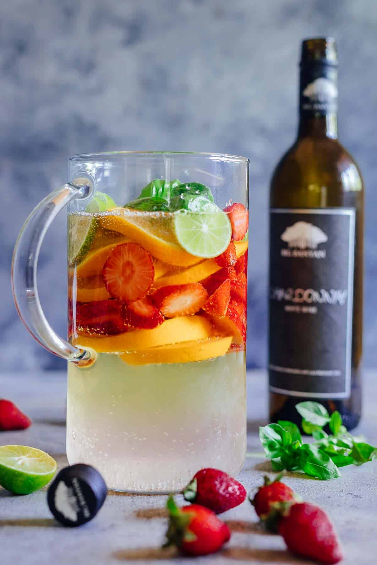 A pitcher of strawberry orange white wine sangria with a bottle of chardonnay in the background