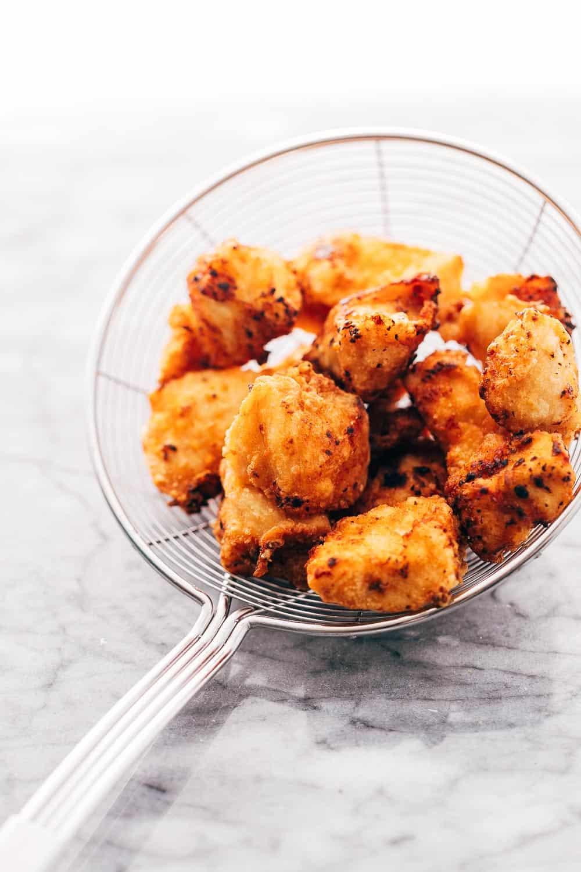 Fried golden crunchy chicken in a frying sieve
