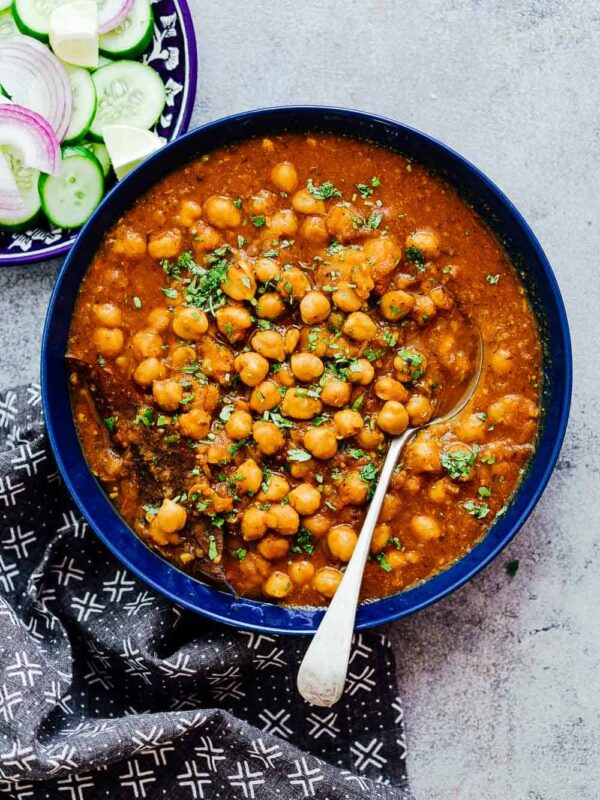 Pressure cooker chana masala in a blue bowl with cucumbers, onions etc on the side