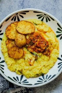 Khichdi served in a black and white bowl topped with fried potatoes and tomato chutney